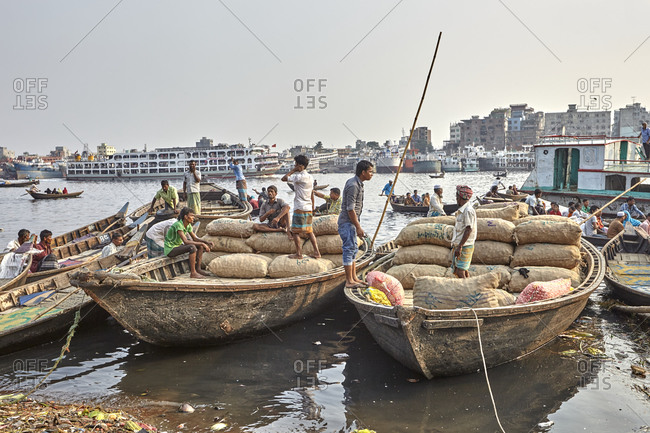 Dhaka, Bangladesh - April 27, 2013: Men in boats at Sadarghat Boat Terminal waiting for passengers