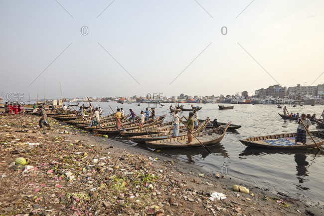Dhaka, Bangladesh - April 27, 2013: Men in traditional country boats waiting for passengers at Sadarghat Boat Terminal