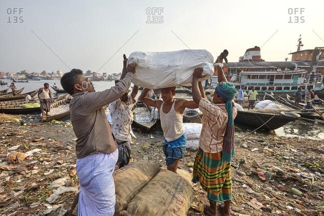 Dhaka, Bangladesh - April 27, 2013: Men loading heavy bags on boats at Sadarghat Boat Terminal