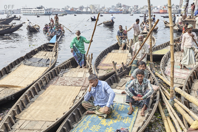 Dhaka, Bangladesh - April 27, 2013: Boatmen sitting and waiting for passengers at Sadarghat Boat Terminal