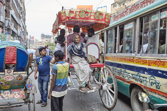 Dhaka, Bangladesh - April 28, 2013: Old woman sitting on the back of a horse cart on a busy street