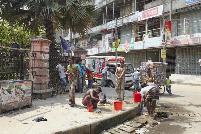 Dhaka, Bangladesh - April 26, 2013: Men bathing directly on a street