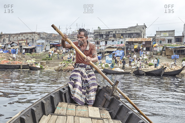 Dhaka, Bangladesh - April 27, 2013: Boatman rowing his boat towards Sadarghat Boat Terminal