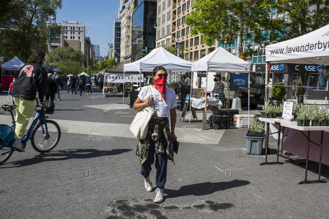 New York City, New York, USA - May 21, 2020: Market -goer wearing bandana as a face covering while shopping at the Union Square Farmer's Market, New York City, USA.