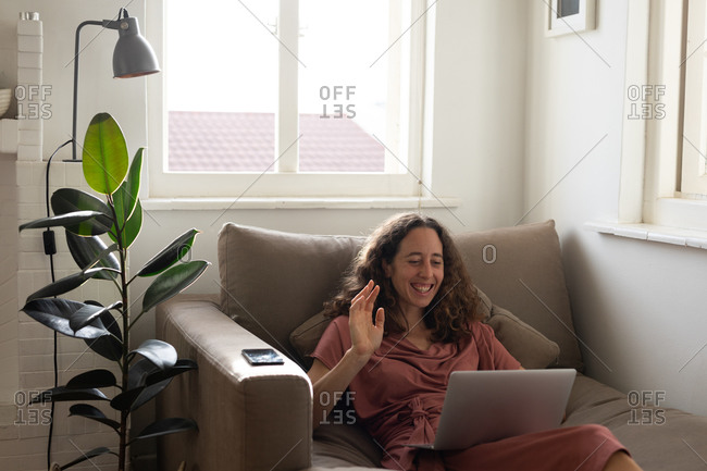 Caucasian woman spending time at home, wearing a pink dress, sitting on a sofa and holding her laptop computer, interacting using social media. Social distancing and self isolation in quarantine lockdown.