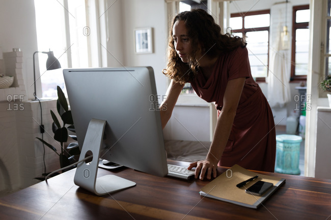 Caucasian woman spending time at home, standing by her desk and working using her computer. Social distancing and self isolation in quarantine lockdown.
