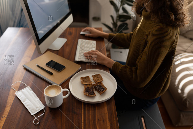 Mid section of a Caucasian woman spending time at home, sitting by her desk and working using her computer, with a snack and coffee put next to her. Social distancing and self isolation in quarantine lockdown.