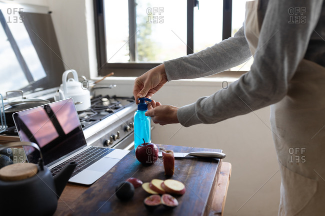 Mid section of a Caucasian woman spending time at home, wearing an apron, cleaning her hands with a sanitizer, preparing for cooking. Social distancing and self isolation in quarantine lockdown.