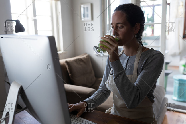 Caucasian woman spending time at home, sitting by her desk and working using her computer, drinking a smoothie. Social distancing and self isolation in quarantine lockdown.