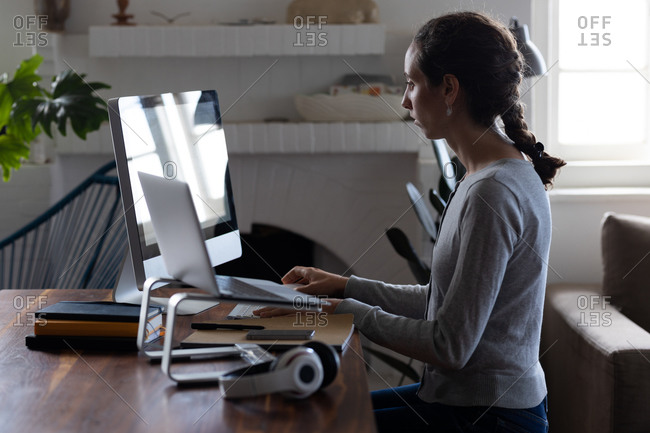 Caucasian woman spending time at home, sitting by her desk and working using her computer. Social distancing and self isolation in quarantine lockdown.