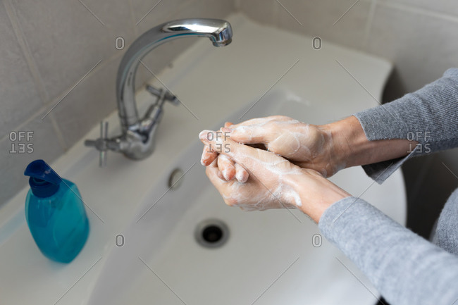 Close up mid section of a Caucasian woman wearing grey sweater, washing her hands with liquid soap. Social distancing and self isolation in quarantine lockdown.