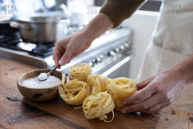 Close up mid section of a Caucasian woman wearing a sweater, preparing pasta for her lunch. Social distancing and self isolation in quarantine lockdown.