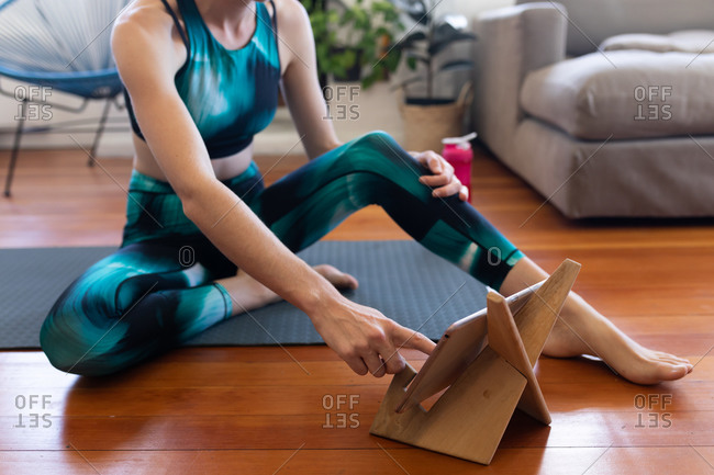 Low section of a Caucasian woman spending time at home, wearing sportswear, sitting on a yoga mat and stretching up, joining online yoga course, using her tablet. Social distancing and self isolation in quarantine lockdown.