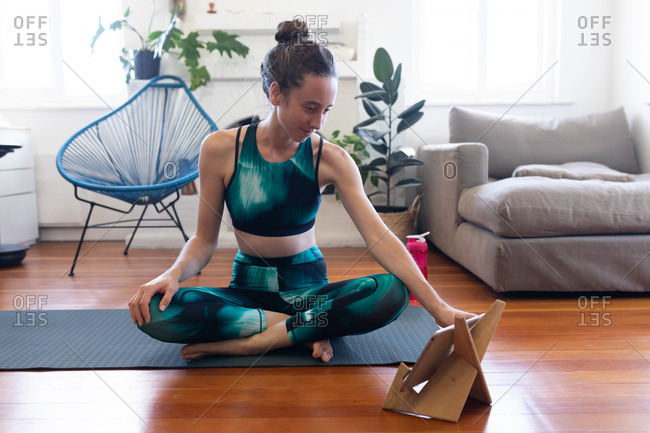 Caucasian woman spending time at home, wearing sportswear, sitting on a yoga mat and stretching up, joining online yoga course, using her tablet. Social distancing and self isolation in quarantine lockdown.