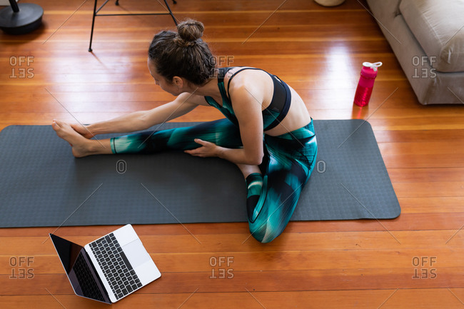 Caucasian woman spending time at home, wearing sportswear, sitting on a yoga mat and stretching up, joining online yoga course, using her laptop. Social distancing and self isolation in quarantine lockdown.