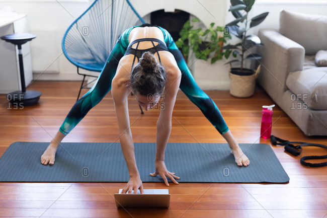Caucasian woman spending time at home, wearing sportswear, exercising on a mat, joining online yoga course, using her laptop. Social distancing and self isolation in quarantine lockdown.