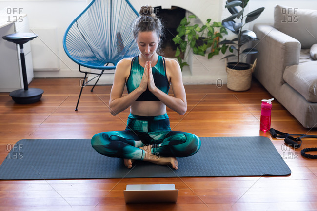 Caucasian woman spending time at home, wearing sportswear, sitting on a mat and meditating, joining online yoga course, using her laptop. Social distancing and self isolation in quarantine lockdown.