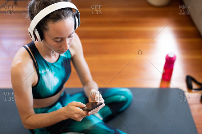 Caucasian woman spending time at home, wearing sportswear and headphones, sitting on a mat and using her smartphone. Social distancing and self isolation in quarantine lockdown.
