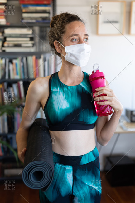 Caucasian woman spending time at home, wearing sportswear and a face mask against coronavirus, covid 19, holding a mat and a plastic bottle. Social distancing and self isolation in quarantine lockdown.