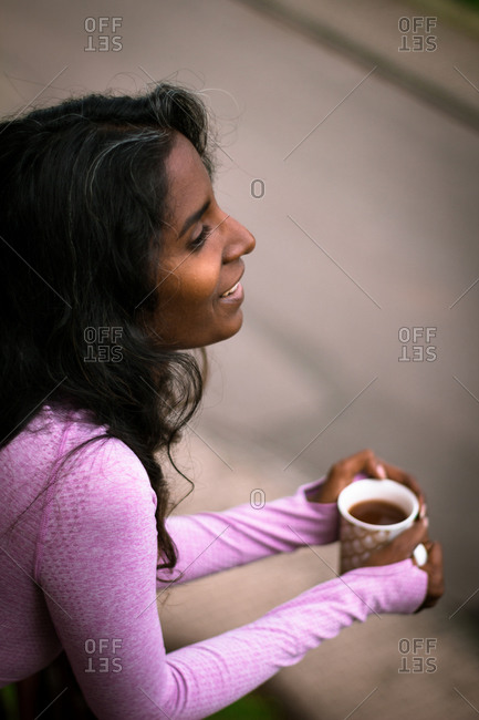 From above view of positive young ethnic lady with long dark hair wearing pink casual clothes holding cup of fresh hot beverage in hands while standing on balcony and looking away