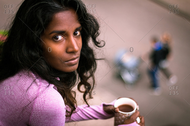 From above view of young ethnic woman with long dark hair wearing pink casual clothes holding cup of fresh hot beverage in hands while standing on balcony and looking at camera