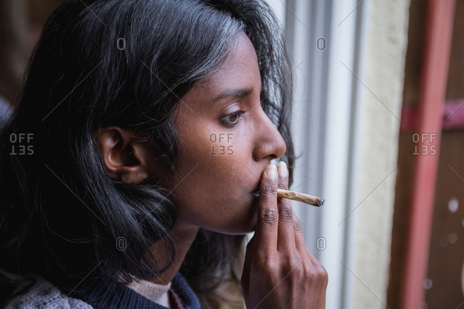 Young Indian female in casual clothing looking away standing on terrace and smoking marijuana roll up while relaxing