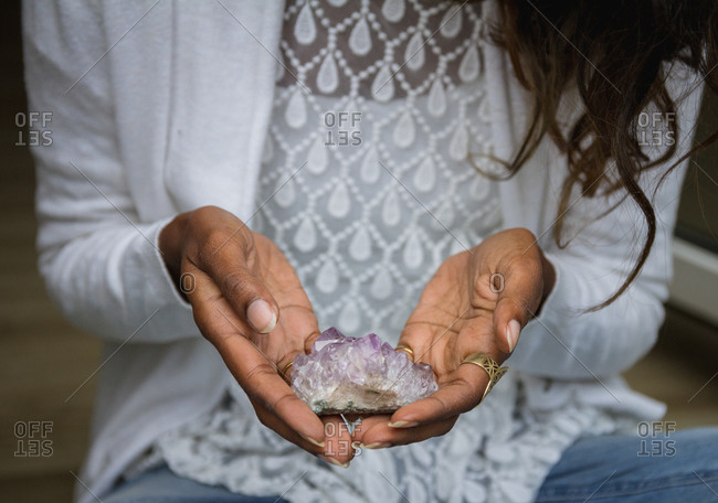 Unrecognizable ethnic female in casual outfit sitting with crystals for rituals