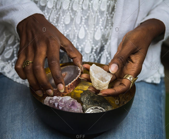 Unrecognizable ethnic female in casual outfit sitting with metal dish with amethyst and agate crystals for rituals