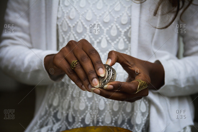 Unrecognizable ethnic female in casual clothes holding small metal gold jar and taking natural balm for lips with finger