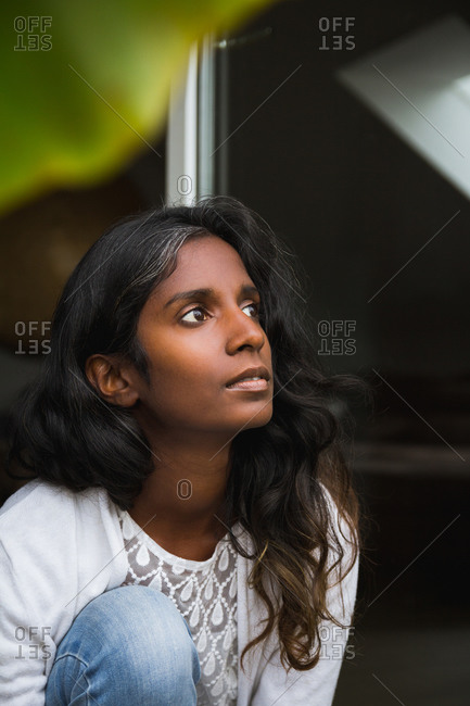 Ethnic female with long wavy hair wearing casual clothes sitting on terrace and enjoying while looking away
