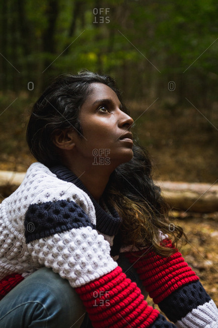 From above of ethnic female in casual sweater and jeans squatting barefoot on ground in wood and looking away
