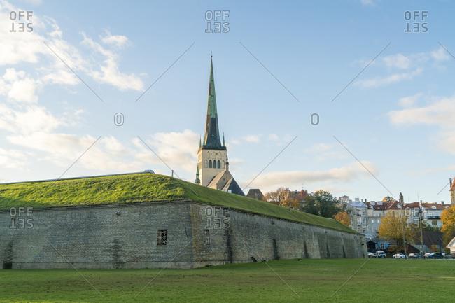 "Estonia, Harju County, Tallinn - October 21, 2017: Old city wall fortification with St Olaf's church ""Oleviste kogudus"""