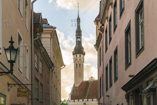 Estonia, Harju County, Tallinn - October 21, 2017: Street in old city with the tower of Tallin town hall in the background by sunset