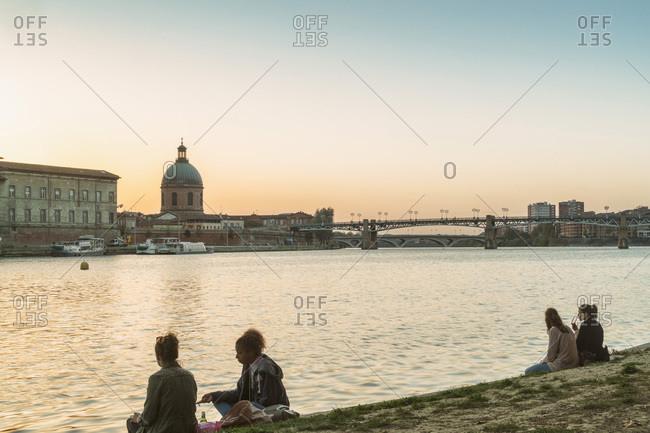 Toulouse, Occitanie, France - October 16, 2017: Couples sitting by Garonne river Chapelle Saint-Joseph de la Grave
