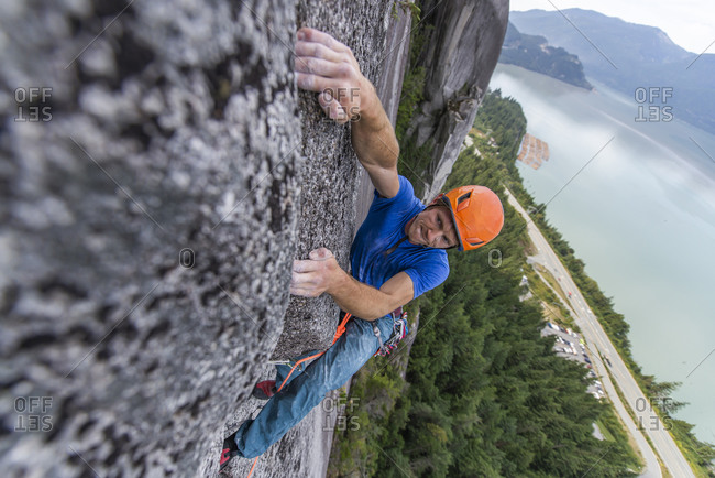 Climber doing hard move on multipitch with ocean view and exposed