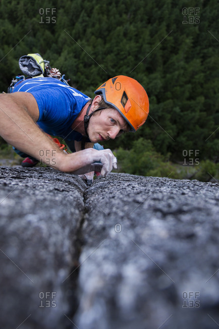 Close up of climber looking very focused on next move while climbing
