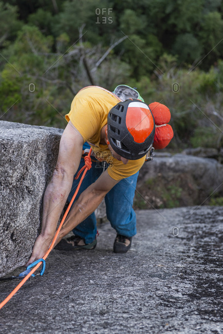 Rock climber looking at his feet while climbing multipitch route