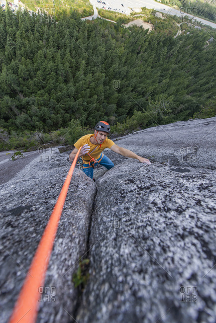 Climber seconding top roping moving rope while climbing multipitch