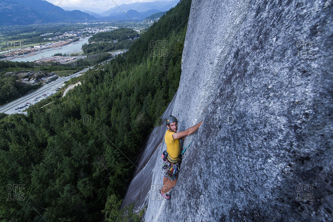 Man rock climbing on Squamish Chief looking at camera city background