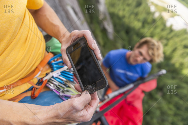 Climber looking at instruction on how to set up portaledge smartphone