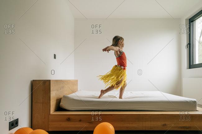 Little girl playing as Hawaiian dancer in parent's bedroom