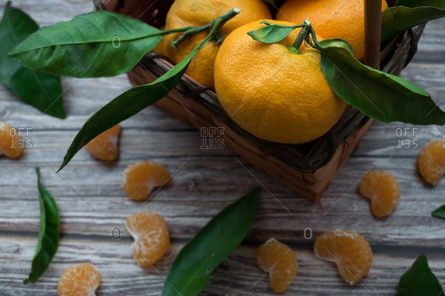 Close-up a fresh tangerine with a leaf inside a basket.