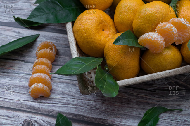 Tangerines inside a box with segments of tangerine on the wooden