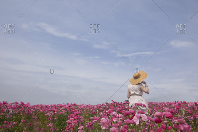 Woman wearing straw hat in pink flowers