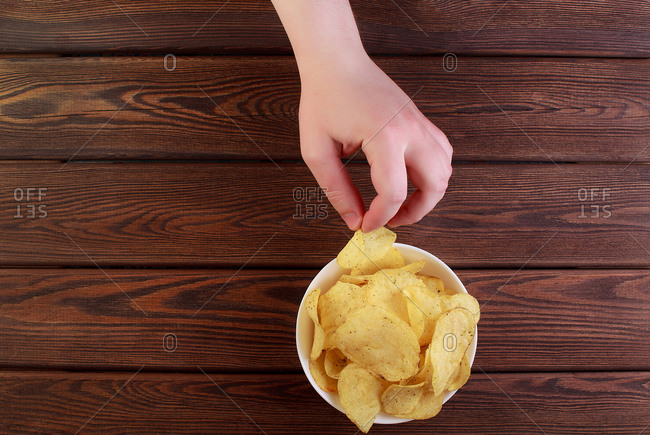 Hand holding potato chips on dish isolated on wooden background