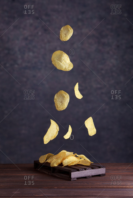 Potato chips fall into a clay bowl on a gray background. Flying chips closeup.