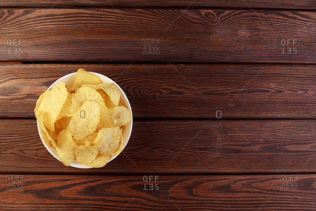 Cheese and chive potato crisp snack in brown bowl on wooden background top view