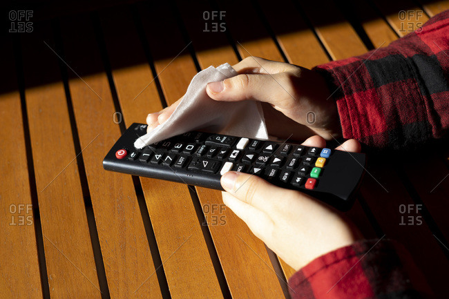 Hands disinfecting a TV remote.
