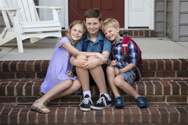 Three Smiling Siblings Sit on Brick Front Porch Steps