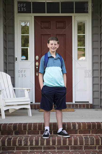 Smiling Tween With Braces Stands on Brick Front Porch Steps
